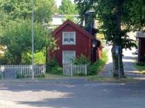 Ett rött hus intill kyrkan